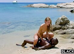 blonde is at the beach drinking a nice load of black pecker